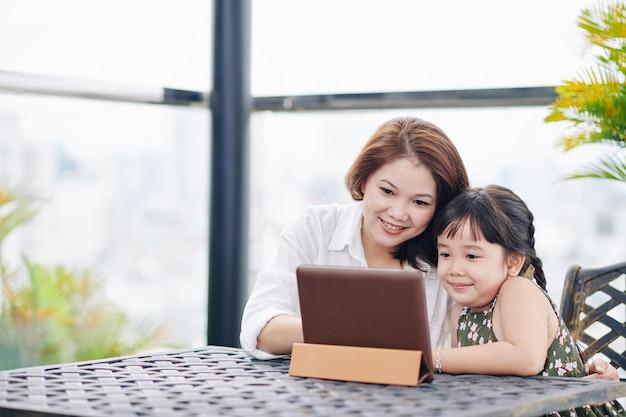 屋外のテーブルに座って、デジタルタブレットで漫画を見ているアジアの母と娘の笑顔