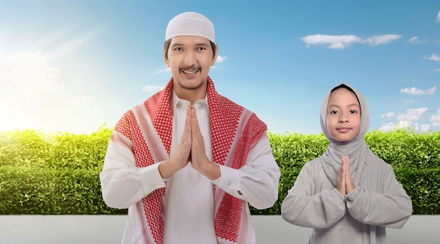 Smiling asian muslim father and daughter praying together