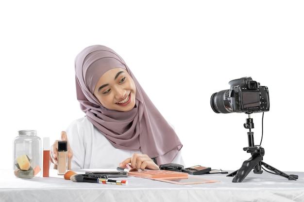 チュートリアルメイクとビデオを作る笑顔のアジアのイスラム教徒の女性ブロガー