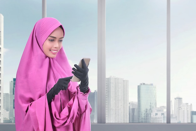 Smiling asian muslim woman messaging on the mobile phone