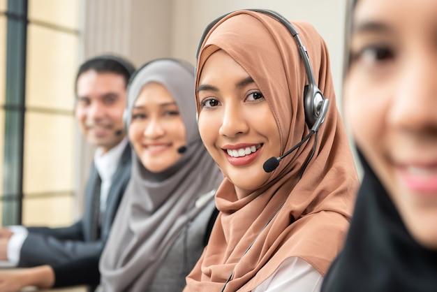 Усмехаясь азиатские мусульманские женщины работая в центре телефонного обслуживания с командой