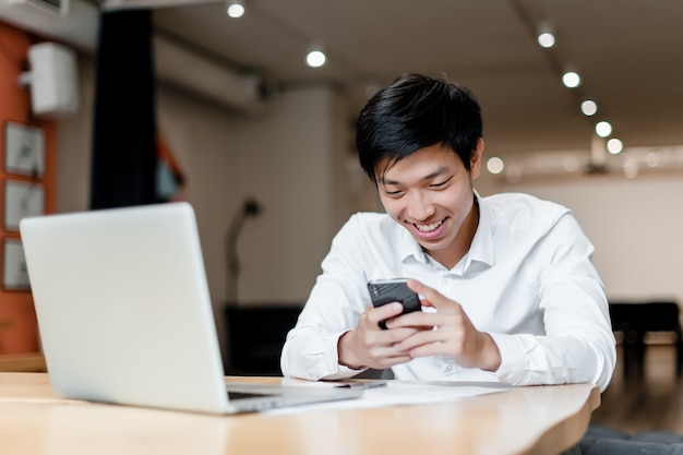 Smiling asian office worker uses phone and laptop