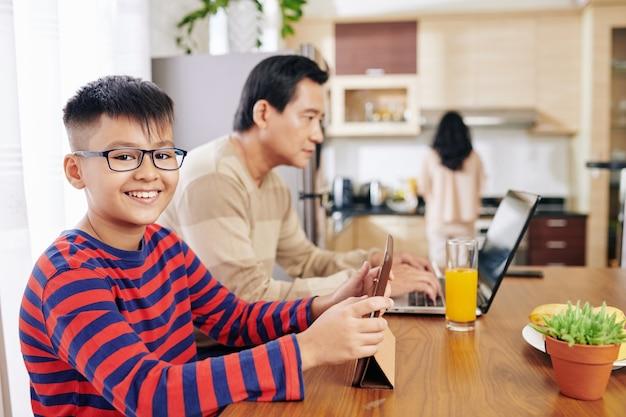 Улыбающийся азиатский мальчик десятилетнего возраста в очках учится онлайн за кухонным столом, его отец работает на ноутбуке поблизости