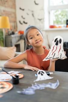Smiling asian schoolgirl holding paper ghost prepared for halloween