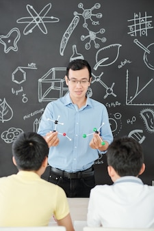 Smiling asian science teacher showing plastic molecular models to curious school stundets