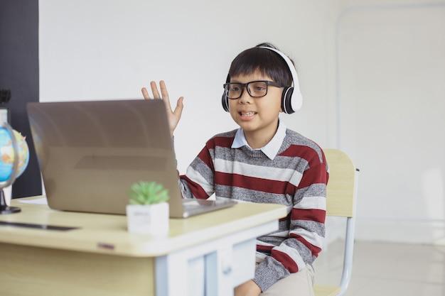 ビデオ通話とノートパソコンへの挨拶をしている笑顔のアジアの学生