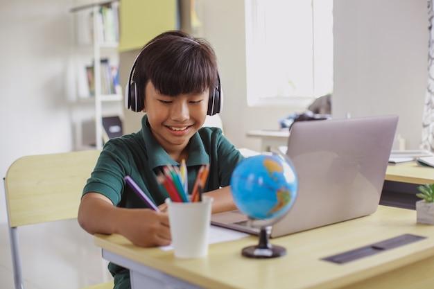 ノートパソコンを使用しながら紙にヘッドフォンで書くアジアの学生の笑顔