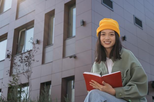 カメラ教育の概念を見て本を読んでアジアの学生の笑顔