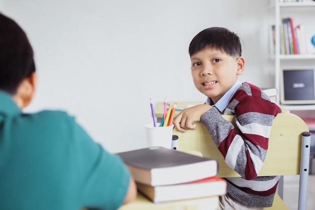 教室でカメラを見ながら椅子に座って笑顔のアジアの学生