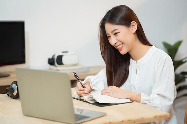집에서 노트북과 노트북을 사용하면서 가르치는 웃고 있는 아시아 교사 여성