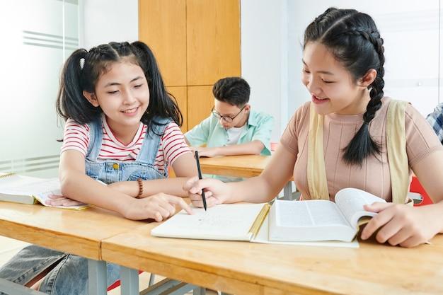 Улыбающаяся азиатская девочка-подросток помогает однокласснику с школьным проектом