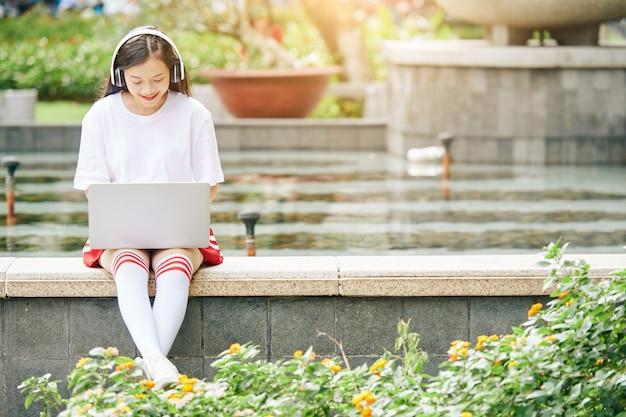 Улыбающаяся азиатская девочка-подросток сидит у фонтана и работает на ноутбуке, слушает музыку и отвечает на электронные письма