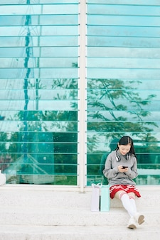 屋外に座って、友達にテキストメッセージを送信し、スマートフォンでソーシャルメディアをチェックして笑顔のアジアの10代の少女
