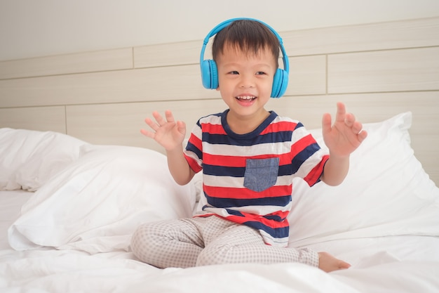 Smiling asian  toddler boy child wearing striped t shirt listening to music in headphones & dancing