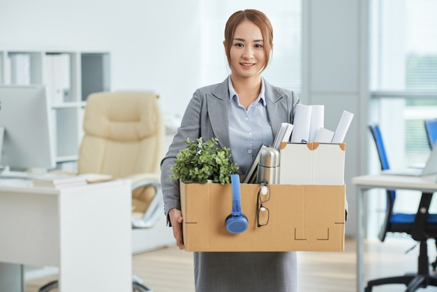 Smiling asian woman in business suit standing in office with belongings in cardboard box