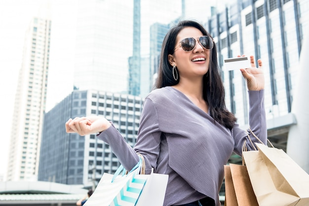 Smiling asian woman carrying shopping bags and showing credit card