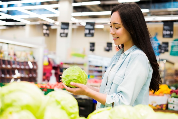Smiling asian woman choosing cabbage in market