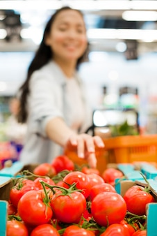 Smiling asian woman choosing tomatoes in supermarket