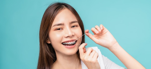 Smiling asian woman cleaning braces on teeth with dental floss on blue background, concept oral hygiene and health care.