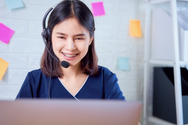 Smiling asian woman consultant wearing microphone headset of customer support phone operator at workplace.