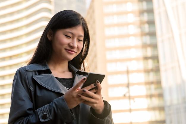 Улыбающаяся азиатская женщина консультируется со своим мобильным телефоном