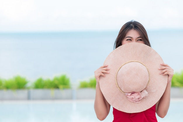 Smiling asian woman covering face with round hat