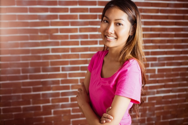 Smiling asian woman crossing arms on brick wall