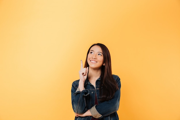 Smiling asian woman in denim jacket pointing and looking up over yellow background