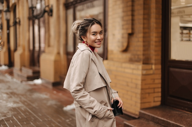 Smiling asian woman dressed in beige autumn coat holding crossbody bag and posing against brick old building