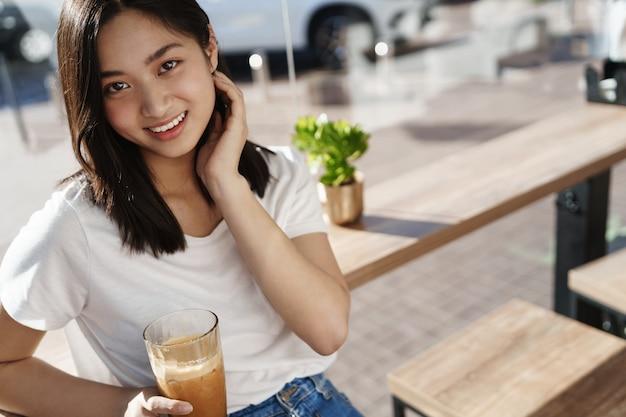 창 근처 커피가 게에서 아시아 여자 마시는 아이스 라 떼를 웃 고.