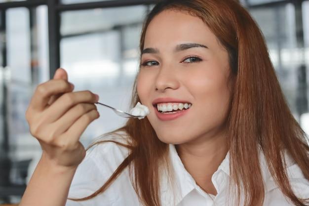 ココナッツクリームケーキの平和を食べる笑顔のアジアの女性