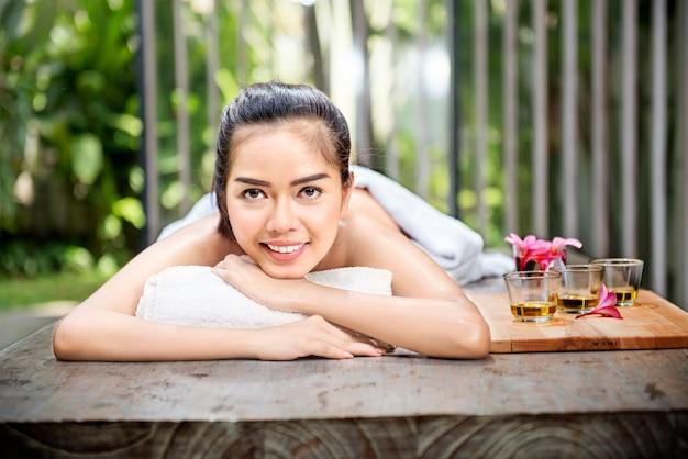 Smiling asian woman enjoying skin care