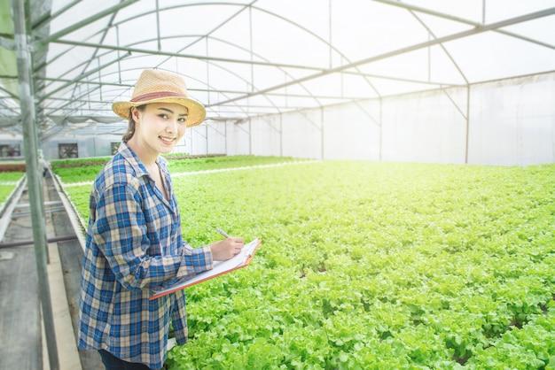 Smiling asian woman farmer hand hold document file in greenhouse green oak hydroponic organic nursery farm.