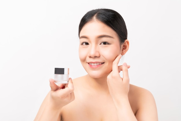 Smiling asian woman hand holding cosmetic bottle