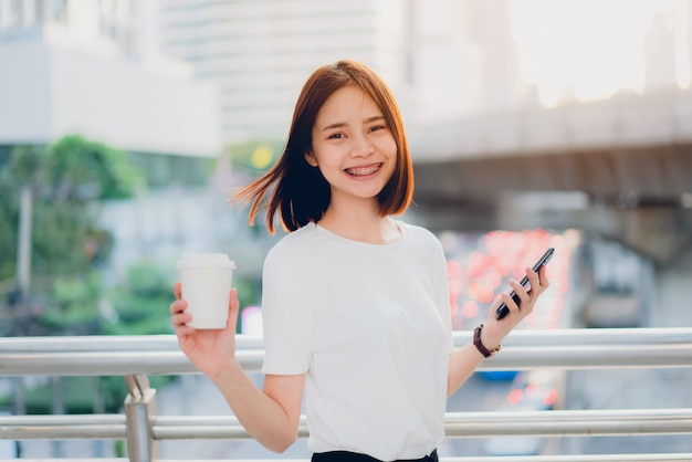 Smiling asian woman holding coffee cup and using smartphone in covered walkway.