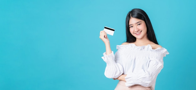 Smiling asian woman holding credit card payment with crossed arms against and looking forward on blue background with copy space.