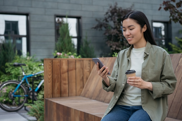 Smiling asian woman holding cup of coffee using mobile phone communication online