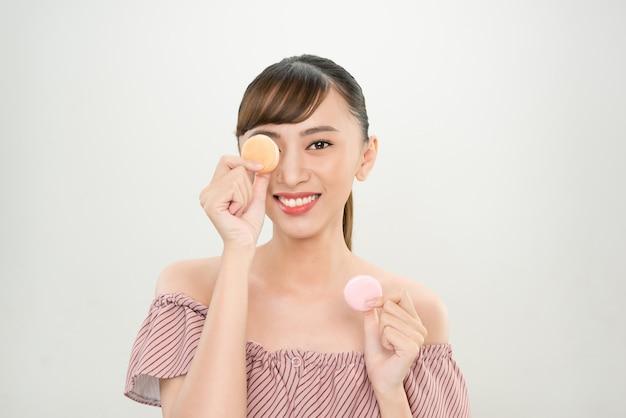 マカロンを目に持つ笑顔のアジア人女性。
