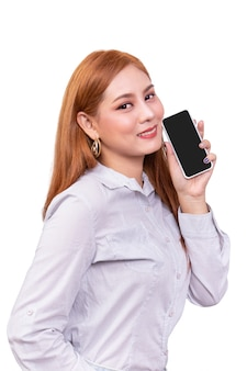 Smiling asian woman holding mobile smartphone with blank black screen standing on white