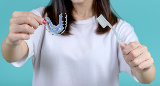 Smiling asian woman holding orthodontic retainer on blue screen background. dental care and healthy teeth.