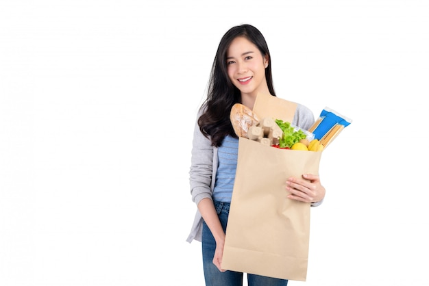 Smiling asian woman holding paper shopping bag full of vegetables and groceries