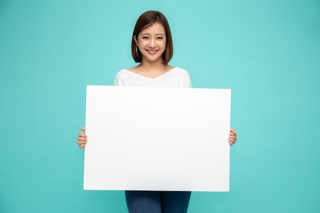 Smiling asian woman holding and standing behind big white poster isolated on light green background