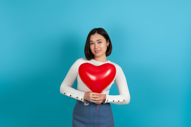 Smiling asian woman holds a red heart-shaped balloon near her chest