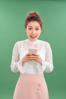 Улыбается азиатская женщина в деловой одежде и печатая на ее фоне ove смартфон.