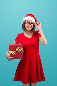 プレゼントボックスを保持している赤いサンタ帽子で笑顔のアジアの女性
