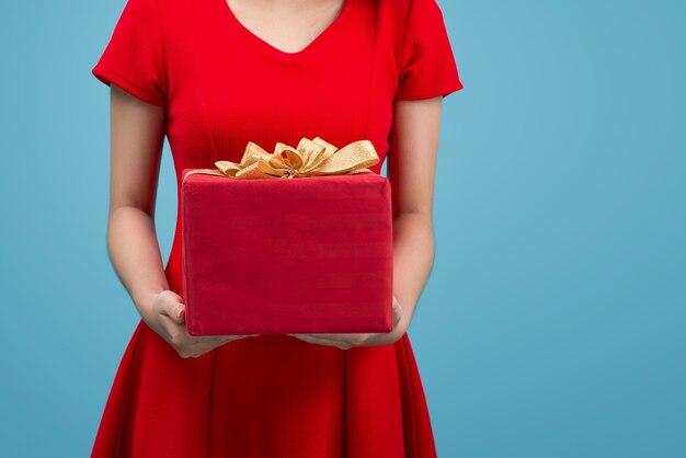 Улыбающаяся азиатская женщина в красной шляпе санта-клауса, держащая подарочную коробку