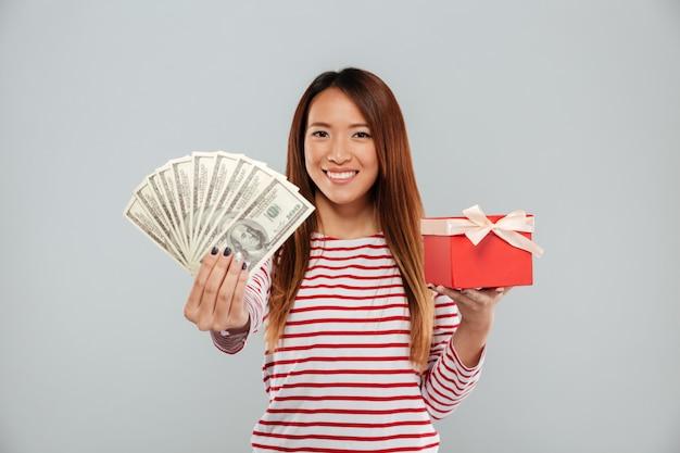 회색 배경 위에 돈과 선물을 들고 스웨터에 웃는 아시아 여자