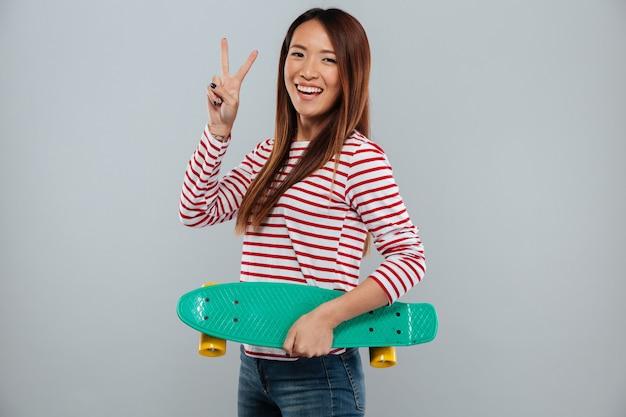 Усмехаясь азиатская женщина в свитере держа скейтборд и показывая мир