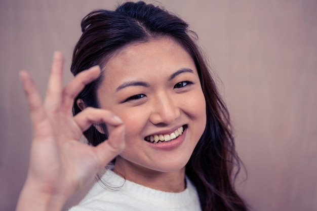 Smiling asian woman making ok sign with hand