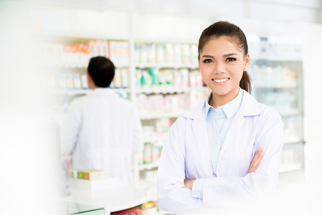 Smiling asian woman pharmacist in pharmacy